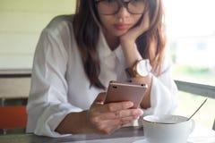 正面图 演奏手机的妇女 她做严肃的面孔wh 库存照片