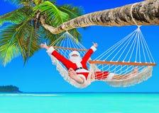 正面圣诞节圣诞老人在吊床放松在棕榈滩 图库摄影
