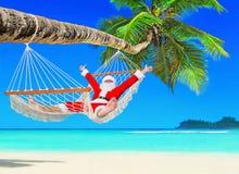 正面圣诞节圣诞老人在吊床放松在棕榈滩 库存照片