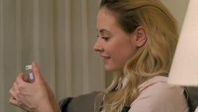 正面女孩使用智能手机,当坐床时 股票视频