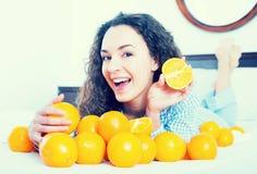 正面女孩在床上的吃桔子 图库摄影