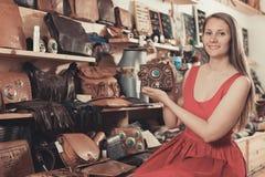 正面妇女在商店选择大手提袋 免版税库存照片