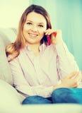 正面妇女在家谈话与她的电话 库存图片