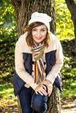 年轻正面妇女摆在树前面的,秋天自然 库存照片