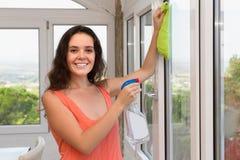 正面妇女清洁窗口在房子里 免版税图库摄影