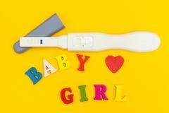 正面妊娠试验、心脏和词'婴孩和女孩'黄色背景的 免版税库存图片