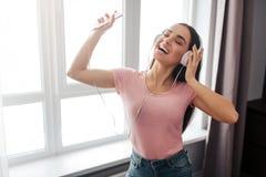 正面年轻女人立场和听到音乐通过耳机在屋子里 她跳舞并且享用 模型微笑 她举行 库存照片