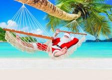 正面微笑的圣诞节圣诞老人在吊床放松在海岛含沙海洋海滩 图库摄影