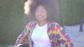 正面微笑的年轻非裔美国人的妇女画象在一个轮椅失去了能力在晴朗的公园 股票录像