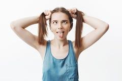 正面情感和表示 年轻悦目皮包骨头的白种人学生女孩在手上的握头发,显示 免版税库存图片