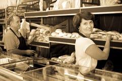 正面成熟面包师用新鲜面包在面包店 免版税库存图片