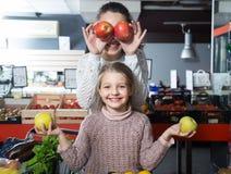 正面摆在部门的妇女和小女孩whith苹果 库存照片