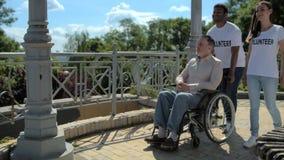 正面的移动式摄影车射击志愿走与一个wheelchaired退休的人 股票录像