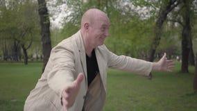 正面祖父和逗人喜爱的孙子方格的衬衣上流的五在公园,微笑 世代概念 影视素材