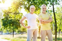 正面站立在公园的退休的夫妇 免版税图库摄影