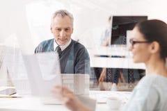 正面老人谈话与他的同事 免版税库存图片