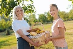 正面资深拿着野餐篮子的妇女和她的孙女 免版税图库摄影