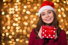 正面逗人喜爱的女孩在有小礼物的圣诞老人帽子 免版税库存照片