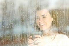 正面青少年看通过一个窗口在一个雨天 库存照片
