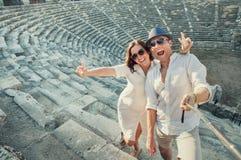 正面年轻夫妇在旁边圆形露天剧场拍自已照片 免版税库存照片