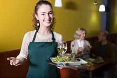 正面年轻女服务员问候顾客 免版税库存照片