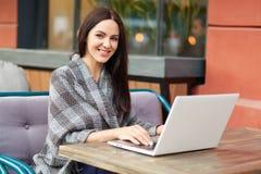 正面optimstic年轻女性博客作者与追随者在网上聊天,有愉快的表示,使用现代便携式计算机并且释放  免版税库存图片