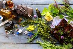 从正统医学到自然医学,从药片和下落到医治草本用设备在一张土气木桌上 库存图片