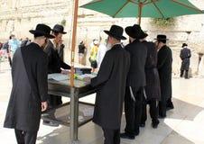 正统犹太人祈祷在西部墙壁在耶路撒冷 免版税库存照片