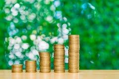 步在桌上的硬币堆在庭院里有绿色背景, f 免版税库存照片