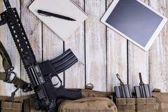 步枪、笔记本和个人计算机片剂接触计算机 顶视图 库存照片