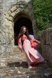 步的一个愉快的嬉皮夫人在英国城堡的古老门道入口附近 库存图片