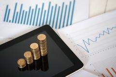 步硬币堆和片剂计算机有财政图表的,企业规划视觉和财务分析 库存照片