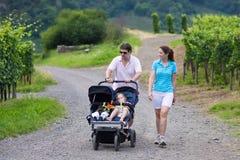 步行与双重婴儿推车的父母 免版税图库摄影