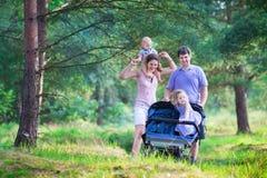 步行与在婴儿推车的两个孩子的活跃父母 免版税库存照片