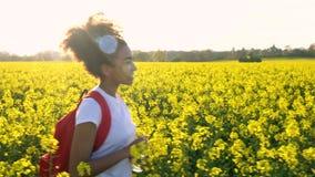 步行与红色背包和水瓶的混合的族种非裔美国人的女孩少年女性少妇在黄色花的领域 股票视频