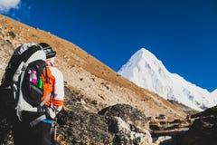 步行与背包的妇女在喜马拉雅山 迁徙对Ev 免版税库存照片