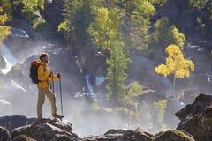 步行与背包的远足者看山河 免版税库存照片