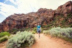 步行在一个美丽的红色岩石峡谷的资深妇女 库存照片