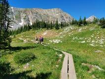 步行在一串板条足迹的三名妇女在落矶山 库存图片