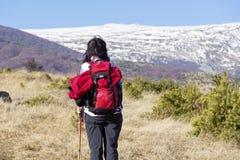 步行在一座高冬天山的旅游妇女 免版税库存图片