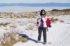 步行在一座高冬天山的旅游妇女 库存照片