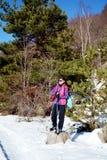 步行在一座高冬天山的被装备的妇女 免版税库存图片