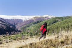 步行在一座高冬天山的被装备的妇女 库存图片
