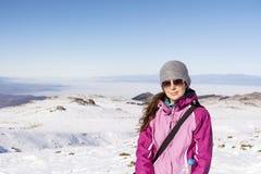 步行在一座高冬天山的被装备的妇女 库存照片
