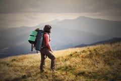 步行在与背包旅行生活方式a的山的少妇 免版税库存照片