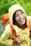 步行在与背包的雨中的愉快的远足者妇女 免版税库存图片