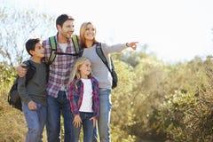 步行在乡下佩带的背包的家庭 免版税库存图片