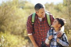 步行在乡下的父亲和儿子 免版税库存照片