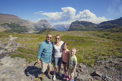 步行在冰川国家公园美丽的山的家庭  库存照片
