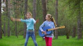 步行在城市公园春天有吉他的两个小白种人学校女孩在森林道路和有乐趣去 股票视频